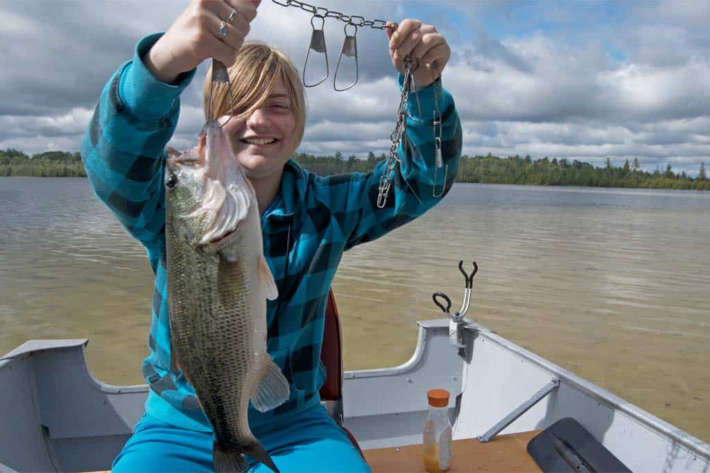 girl holding up bass fish after catching